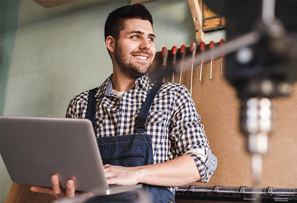 Mann mit Laptop in der Werkstatt