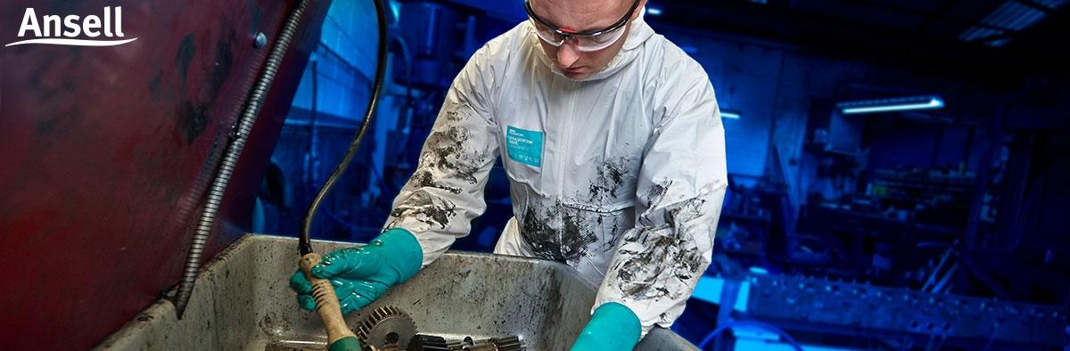 Mann im Schutzanzug und mit Handschutz in der Werkstatt