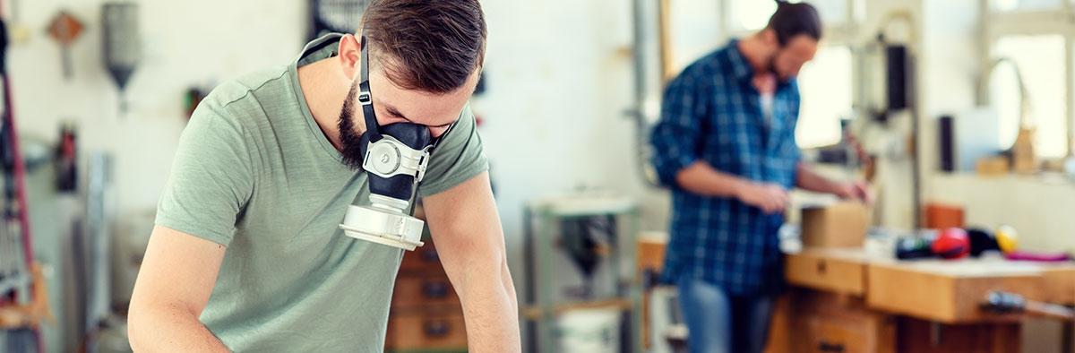 Männer in Werkstatt mit Atemschutzmasken