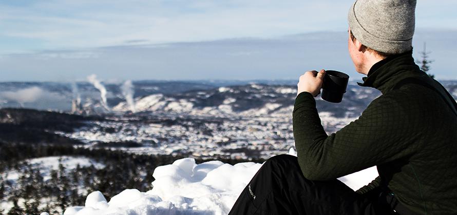 Mann sitzt mit einer Tasse Kaffee in der Hand auf einem Berg im Winter und trägt eine Wintermütze