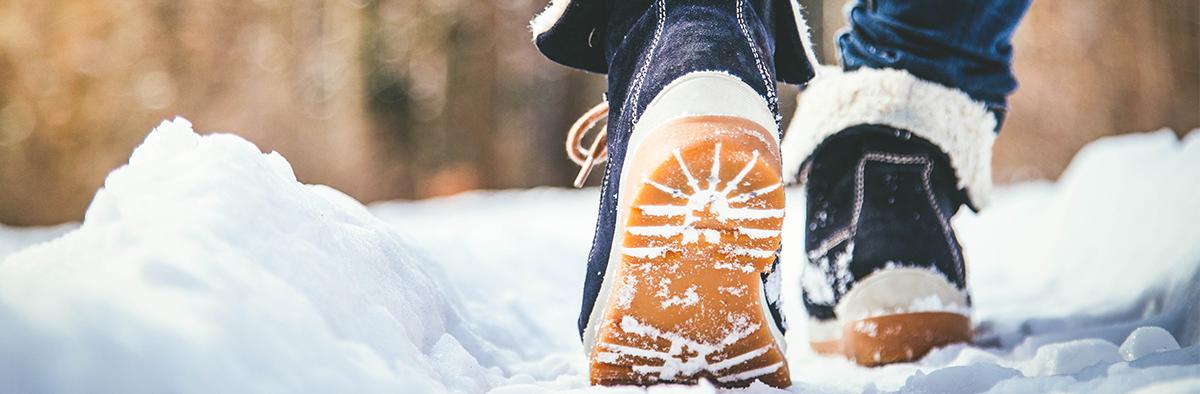 Person läuft mit Winterstiefeln im Schnee